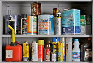 Picture of a shelf with household hazardous waste on it, including paint, pesticides, bleach, gasoli