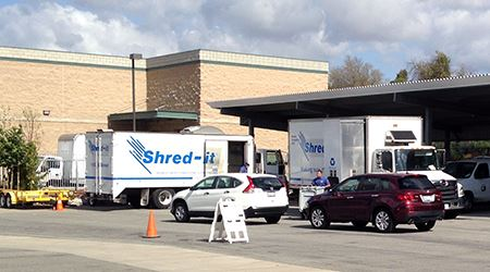 People moving carts of paper from private vehicles to shredding trucks