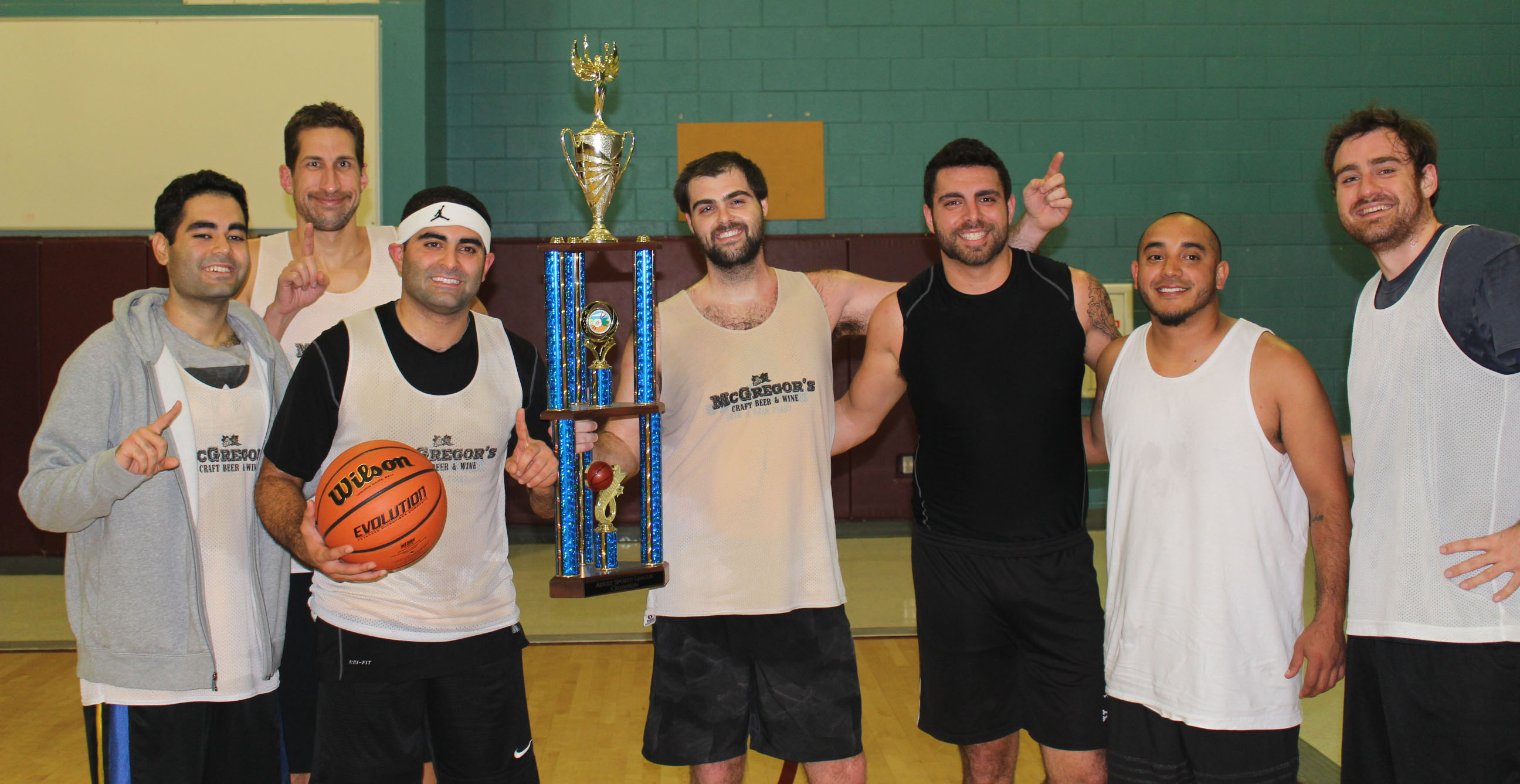 Adult basketball team with trophy